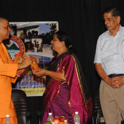 Swamiji Hands Over The First Copy To Ms. Malini Hm Pshs School
